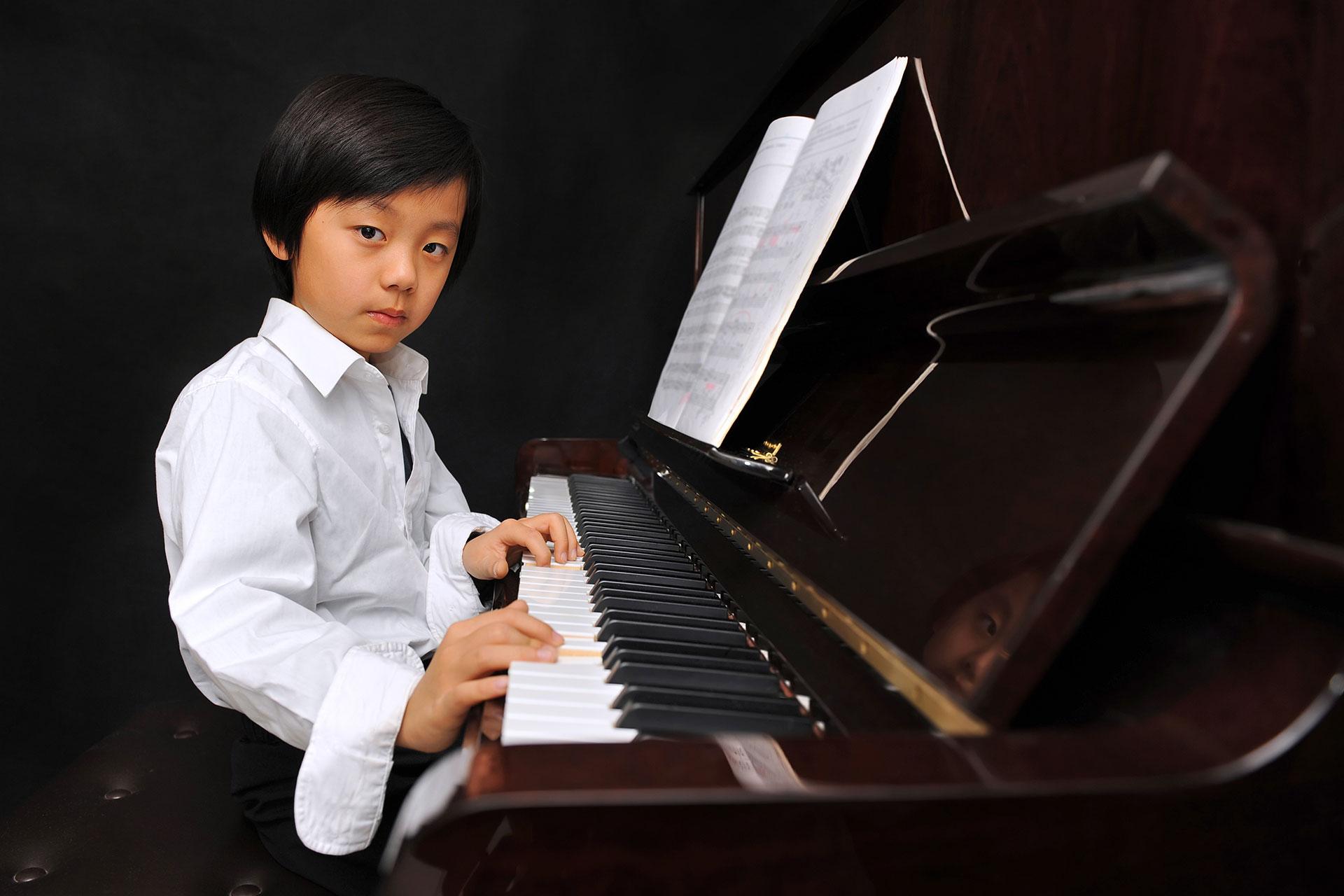 Boy sitting at the piano, Quassica Piano Lesson